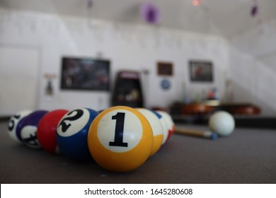Billard balls on a pool table in the garage. There is a bar in the background  with pictures and decorations.