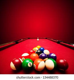 Billards pool game. Color balls in triangle, aiming at cue ball. Red cloth table