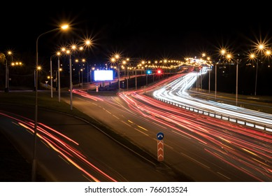 A Billboard between night roads with the light from the lamps