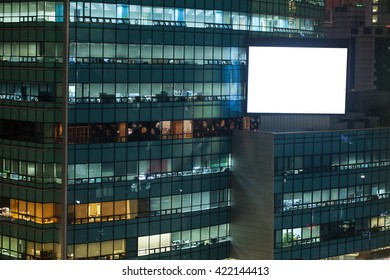 Billboard with blank space on modern office building in evening