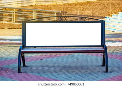 Billboard with blank white copy space for text message or content, mock up banner on a city bench, illuminated by sunlight