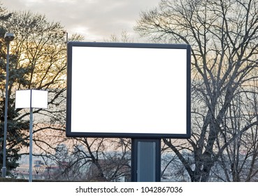 Billboard with empty white screen and trees in the background