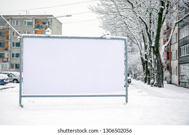 Billboard mockup poster stand in the street. Winter, snow and cold