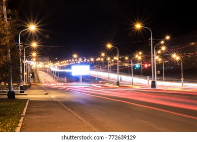 A Billboard at night roads amid signs of headlights of cars