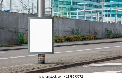 Billboard standing next to a road.