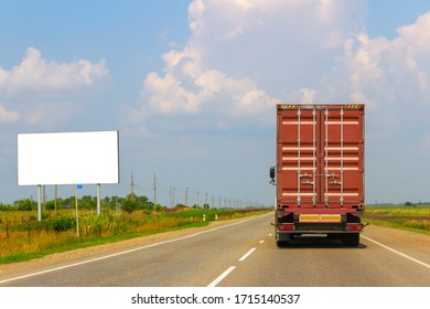 billboard with white background on the road that a truck is driving on a clear summer day