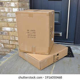Billericay, Essex, United Kingdom, February 13, 2021. Two brown cardboard boxes outside of a house front door step. Online shopping delivery.  Billericay, Essex, United Kingdom, February 13, 2021.