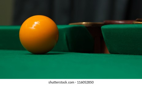 The billiard ball slides in a billiard pocket.