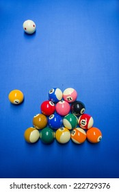 Billiard balls arranged for a game of straight pool for competition. On a blue cloth.