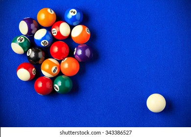 Billiard balls in a blue pool table. Horizontal image viewed from above.