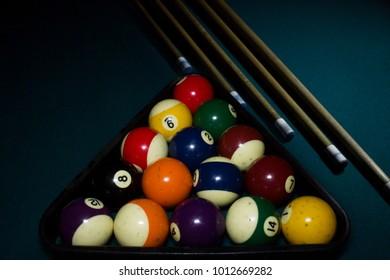 billiard balls inside the triangle with four cue sticks on green billiard table
