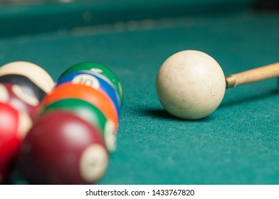Billiard balls and a stick on a green table. Billiard balls isolated on a green background