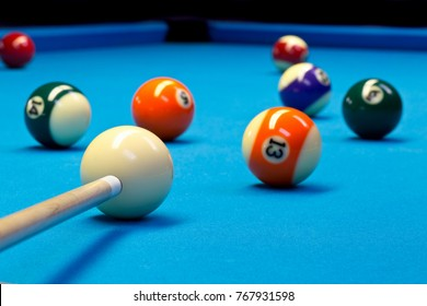 Billiard pool eightball taking the shot on billiard table with blue cloth, selective focus on white ball