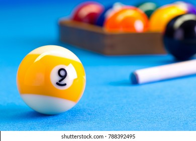 Billiard pool game nine ball with cue and nineball balls set up on billiard table with blue cloth