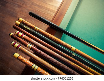 Billiard sticks for your poster or cover of playing club. Billiard cues on pool table, traditional equipment for snooker game. Background for your concept hobby and leisures with place for lettering.