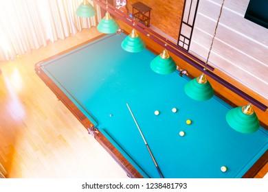 Billiard table close up. Playing billiard. Billiards balls and cue on green billiards table. Billiard sport concept. Pool billiard game. Home interior.