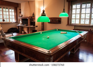 Billiard table with mock tiger skin rug on parquet floor