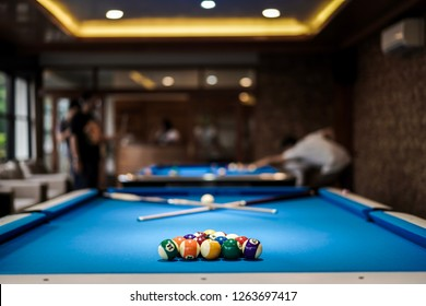 Billiard table setting with people play in background