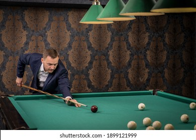 the billiards player aims at the ball to hit and pocket it