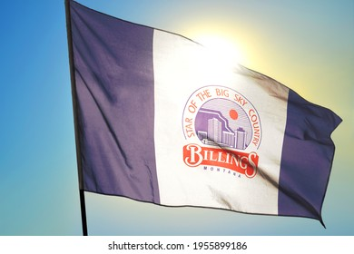 Billings of Montana of United States flag waving on the wind in front of sun