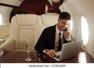 Billionaire or rich businessman flying first class and working on plane with laptop and glass of champagne. Private jet