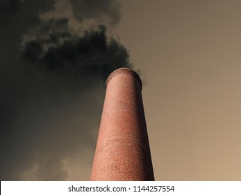 Billowing brick smokestack pouring pollution into a dark stormy sky.