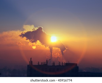 billowing smoke into the atmosphere at sunset