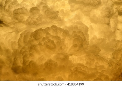 Billowy fluffy golden sunset storm cloud background.