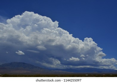 billowy white and gray clouds over desert