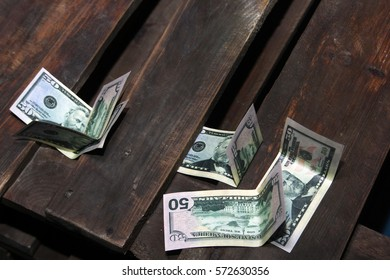 bills of fifty dollars on a wooden table