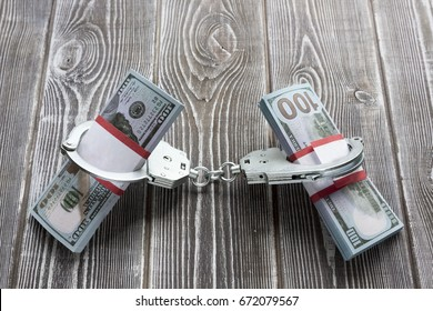 Bills of one hundred dollars in handcuffs, like hands. In the background there is a table made of wood. Idea: Detention of an attacker, trial, release on bail, arrest, theft of money, bribe.