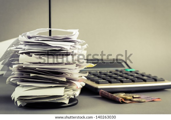 Bills in paper nail with calculator and money