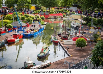 Billund, Denmark - July 27, 2017:  Ships docks at the harbour built of lego bricks. People walking through the Lego city in Legoland, Denmark