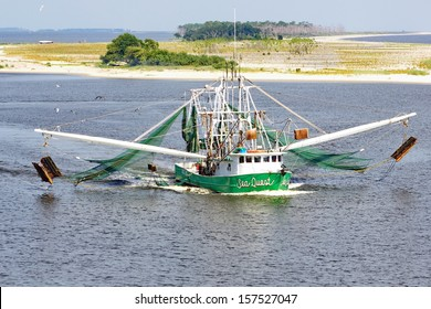 BILOXI, MISSISSIPPI - AUGUST 8:  A commercial shrimping boat heading through Biloxi Bay Channel, with nets extended.  The shrimping industry is vital to segments of the Biloxi, Mississippi, economy.
