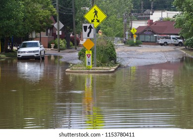 BILTMORE FOREST, NORTH CAROLINA, USA - MAY 30, 2018: A flooding river covers a street and sidewalk with water