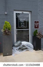 BILTMORE FOREST, NORTH CAROLINA-MAY 30, 2018: A glass store door has sand bags piled on the ground in front of it to protect from rising flood waters on May 30, 2018 in Bltmore Forest, North Carolina