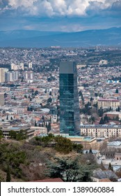 Biltmore Hotel. Tbilisi, Georgia. View Of New Glass Skyscraper Surrounded By Buildings Of Soviet Time .