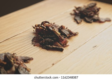 Biltong (beef jerky) on a wooden board, this is a traditional food snack that can be found in South Africa.