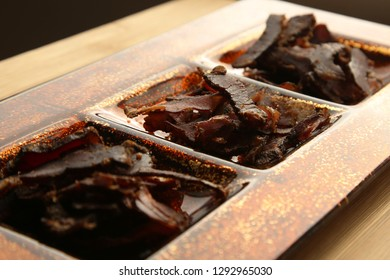 Biltong (dried meat) on a wooden board, this is a traditional food snack that can be found in South Africa.