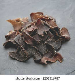 Biltong (protein snack) on a black slate tile, this is a traditional food snack that can be found in South Africa.This image has selective focusing.