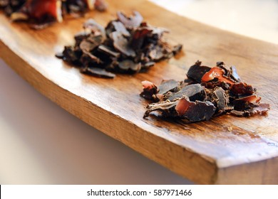 Biltong tasting platter with three piles of cured meat on wooden board
