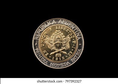 A bimetallic one peso coin from Argentina isolated on a black background