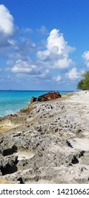 Bimini, Bahamas - 18 Nov 2018: A rocky beach, turquoise blue ocean in the background, sunken boat, and blue skies of a sunny day. Bright picture with no alterations. Beautiful paradise like day.