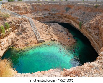Bimmah sinkhole, one of the world most beautiful natural sinkhole in the Sultanate of Oman. Tourists can swim in the clear turquoise waters to cool off from the desert's heat from the nearby Wahiba