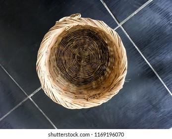 Bin handmade from bamboo for environment on black floor.