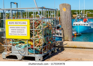 A bin labeled ROPE RECYCLING on a wharf. The bin is for marine rope and is partly full. Ocean with a fishing boat in the background, blue sky above.