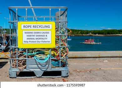 A bin labeled ROPE RECYCLING on a wharf. The bin is for marine rope and is partly full. Ocean in the background, blue sky above.
