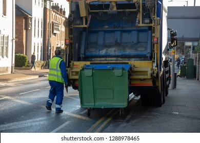 bin lorry or refuse truck collects waste from a green dumpster with council bin worker operating mechanism in a yellow vest