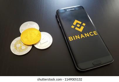 Binance cryptocurrency exchange logo on phone with bitcoin ripple litecoin and ethereum. Copenhagen / Denmark - 08 04 2018