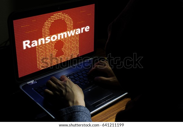 Binary code yellow key pad with the word Ransomware attack on desktop screen notebook red background, cyber attack internet security concept